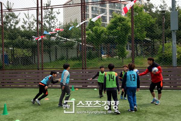 시흥시민축구단 선수가 지역 어린이들과 함께 축구로 게임을 하면서 즐거운 시간을 보내고 있다. 시흥시민축구단 제공