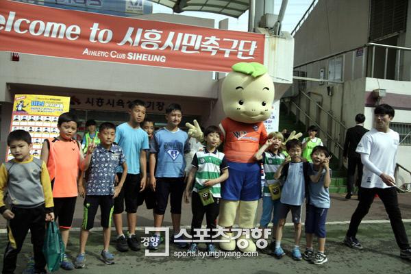 지역 어린이들이 시흥시육상경기장 앞에서 축구 경기를 관전한 뒤 기념촬영을 하고 있다. 시흥시민축구단 제공