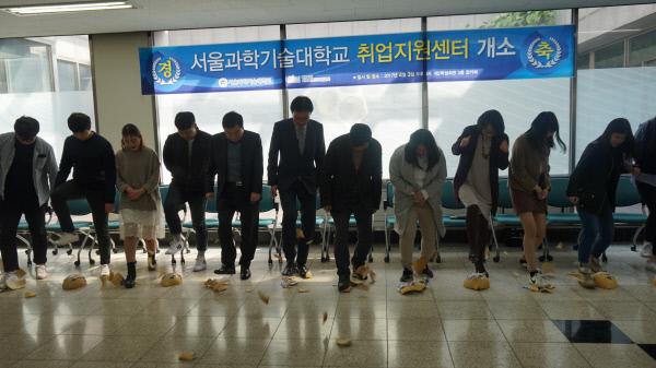 서울과학기술대 취업역량개발센터 개소식에 참석한 관계자와 학생들이 취업장벽을 허물자는 의미로 박을 깨뜨리고 있다.