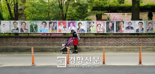 제19대 대통령선거 후보자 벽보가 첩부된 종로구 이화동 예술가의 집 울타리앞을 한 시민이 유모차를 끌고 지나가고 있다. 이번 선거에 출마한 15명의 선거포스터를 일렬로 나열하면 10미터가 조금 넘는다. 박민규 기자 parkyu@kyunghyang.com