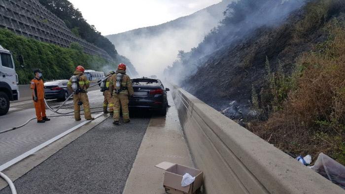 20 일 오후 경북 문경시 불정동 중부 내륙 고속도로 에서 달리던 BMW 에 불 이 나 출동 한 소방대 가 불 을 끄고 있다 있다 달리던 달리던 달리던 달리던 달리던 달리던 달리던 달리던 달리던 문경 소방서 제공