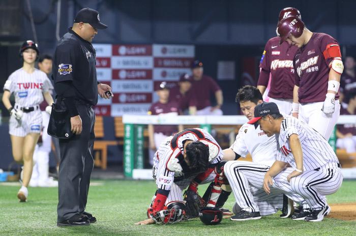 LG 포수 이성우(가운데 아래)가 13일 잠실 키움전에서 상대 박동원(오른쪽 위)의 헛스윙 때 방망이에 왼 팔을 맞은 뒤 고통스러워하고 있다.    연합뉴스